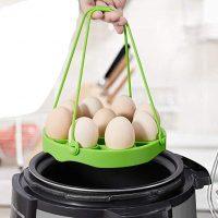 Photo principale du cuiseur à oeuf silicone vert avec des œufs dans le panier de cuisson au dessus d'une marmite d'eau bouillante.